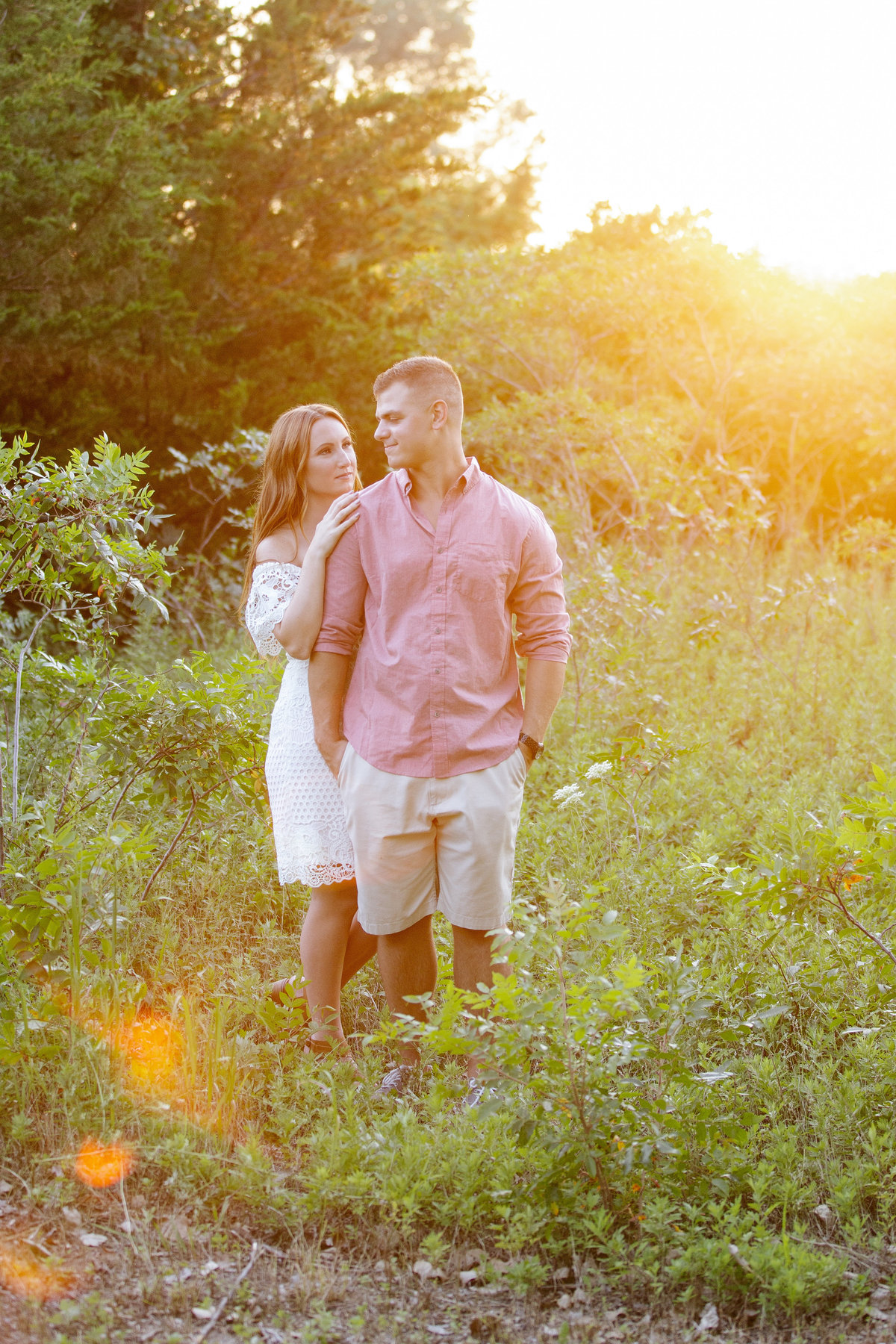 engaged couple stand in field at sunset in manasquan