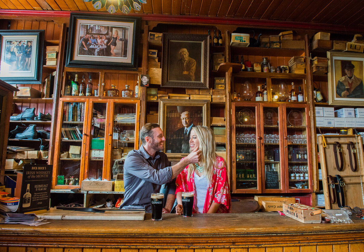 Young couple in colourful clothes sitting in an old Irish Pub in Dingle with pints of Guinness