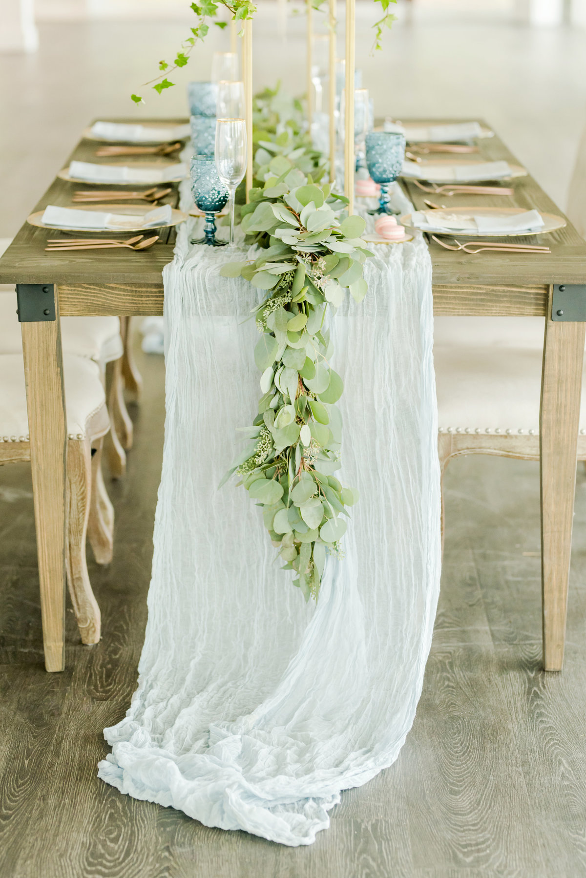 Barn table covered with white linen table runner and place settings for wedding