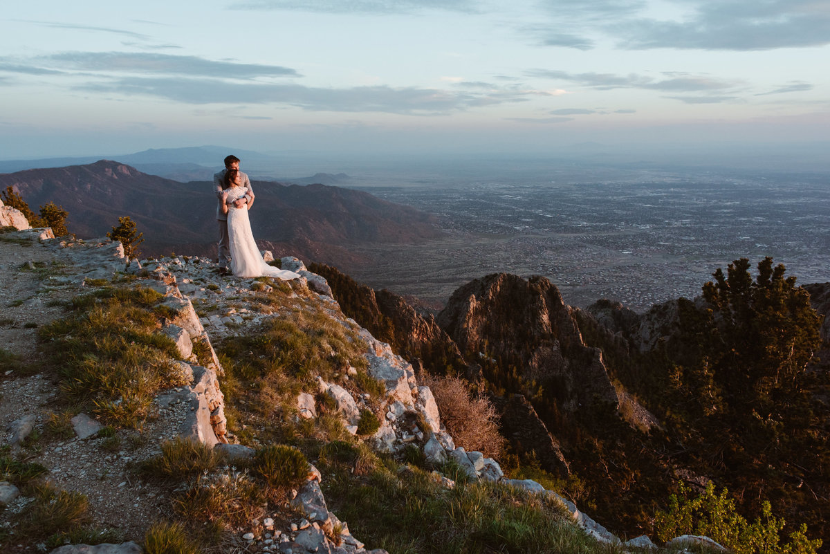 Elopement wedding couple stands on Sandia Crest mountain watching sunset in Albuquerque.