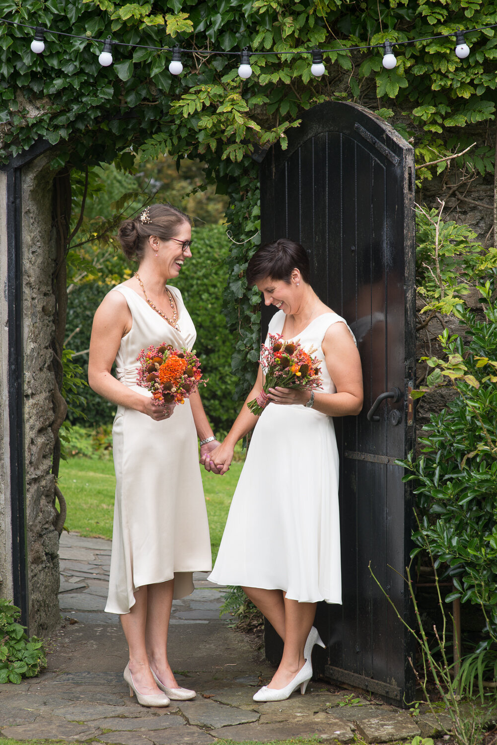 two brides holding hands at garden gate with fairy lights