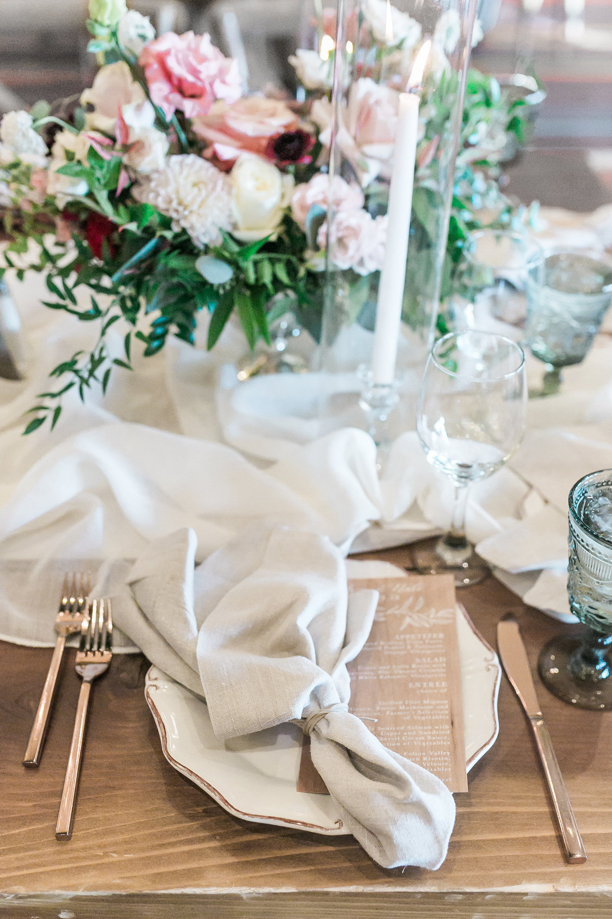place setting for a Lake Tahoe wedding with wood menus and gold flatware with aurora linen from La Tavola