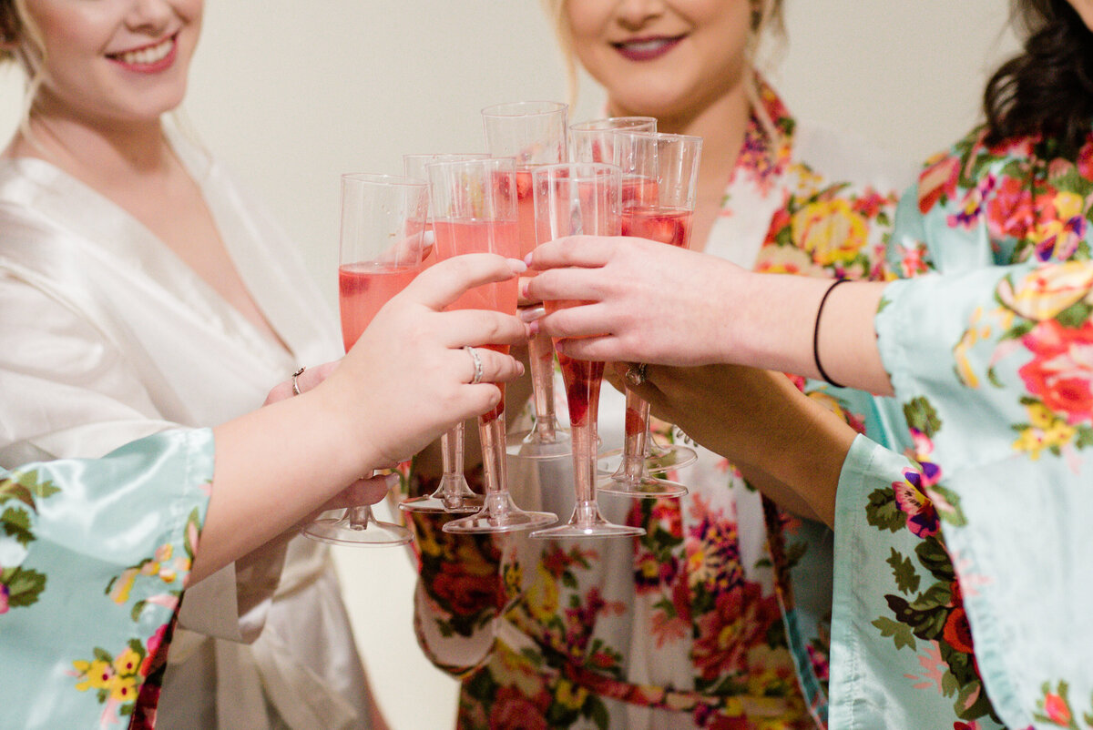 A bridal party celebrating with mimosas on wedding day
