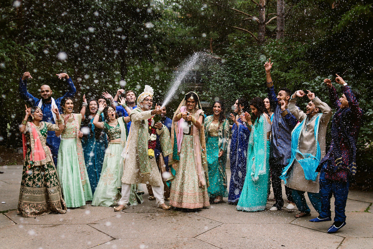 Indian wedding party spraying champagne