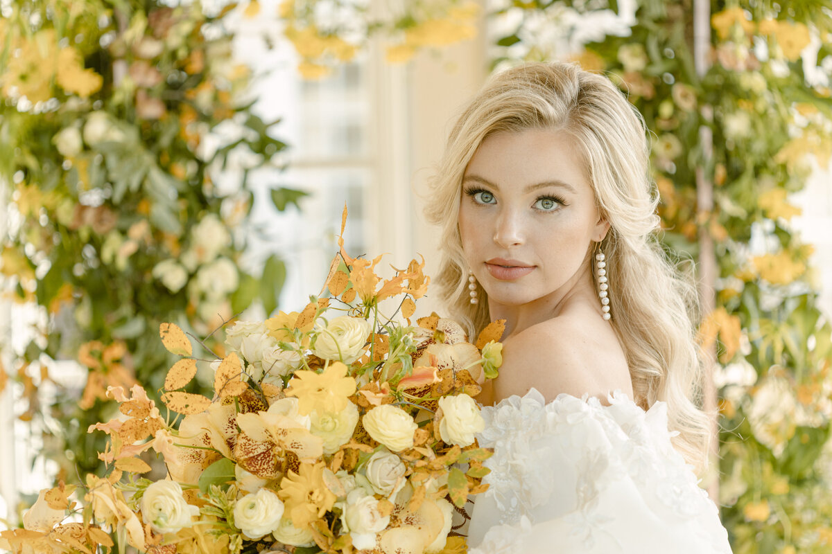 Beautiful bride holds yellow bouquet in front of lush floral arch on her wedding day