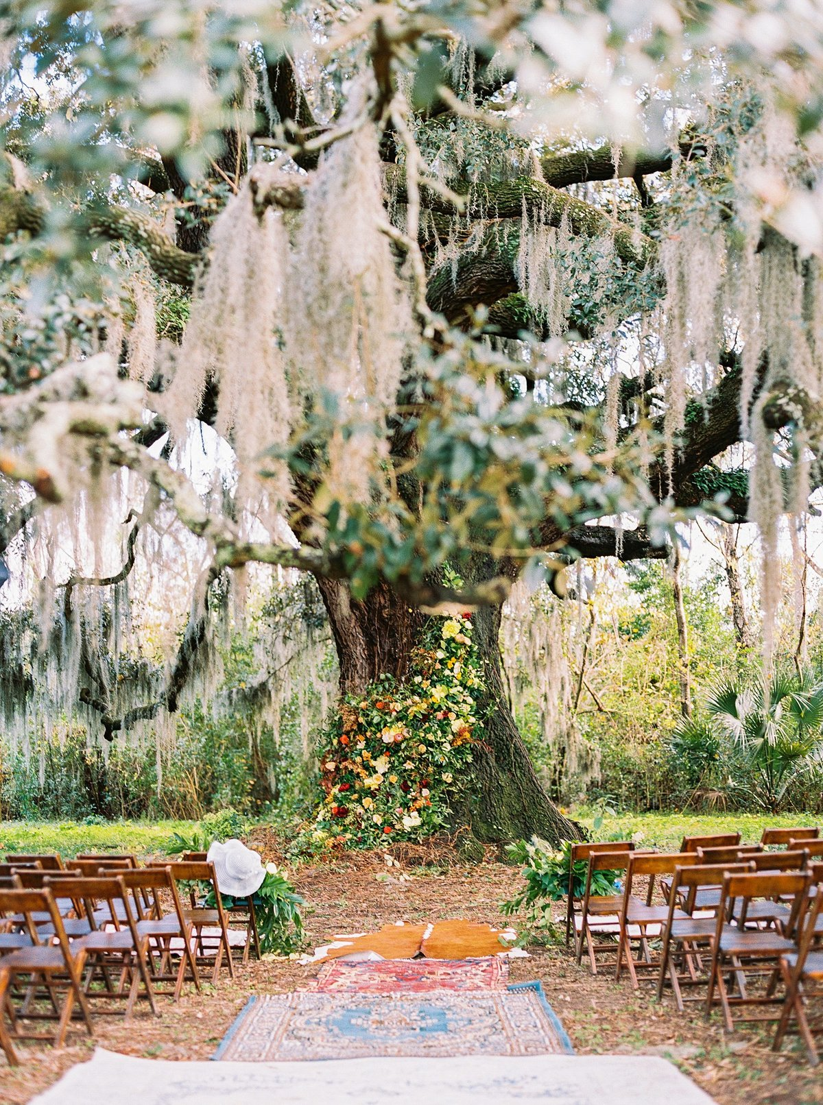 Vintage rugs line the aisle of an outdoor wedding.