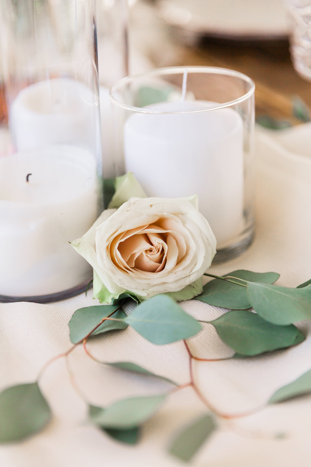 a blush rose with loose greenery and white candles atop a table at a wedding in Las Vegas