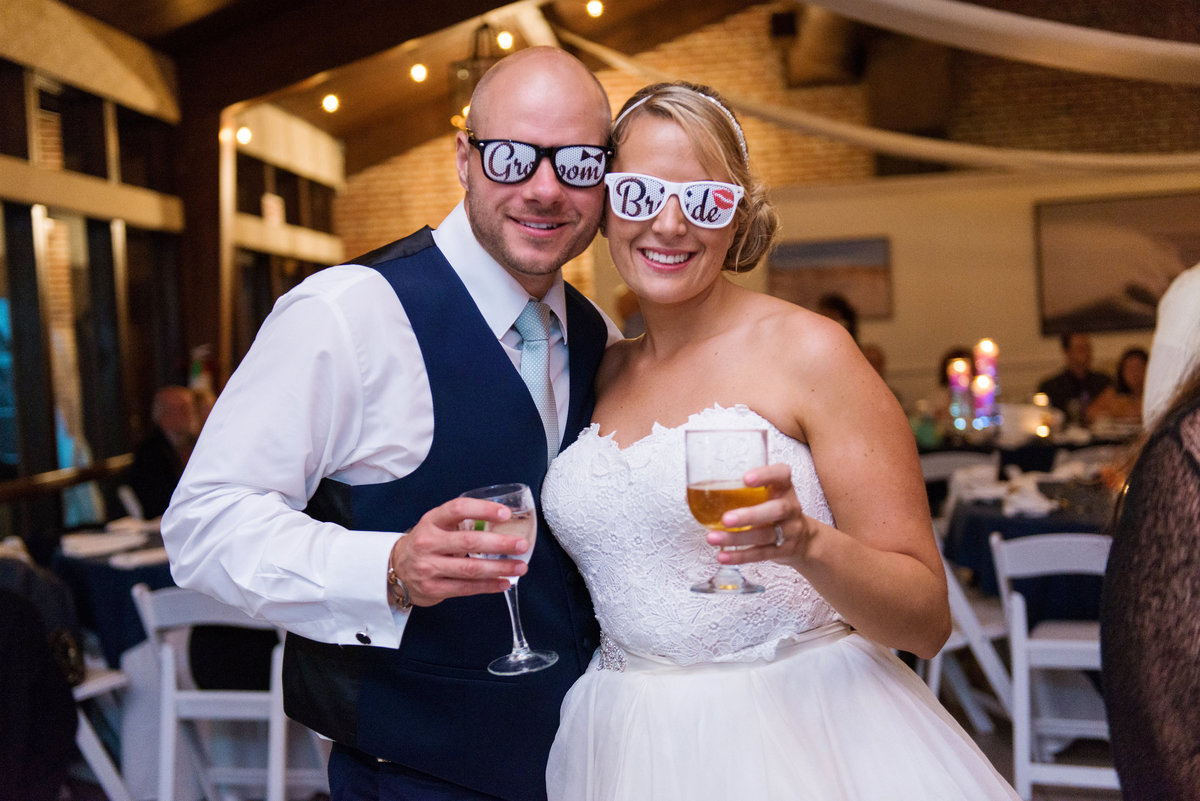bride and groom with drinks and sunglasses during wedding reception at Pavilion at Sunken Meadow