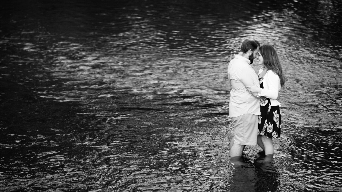 A romantic engagement portrait in shallow water river.