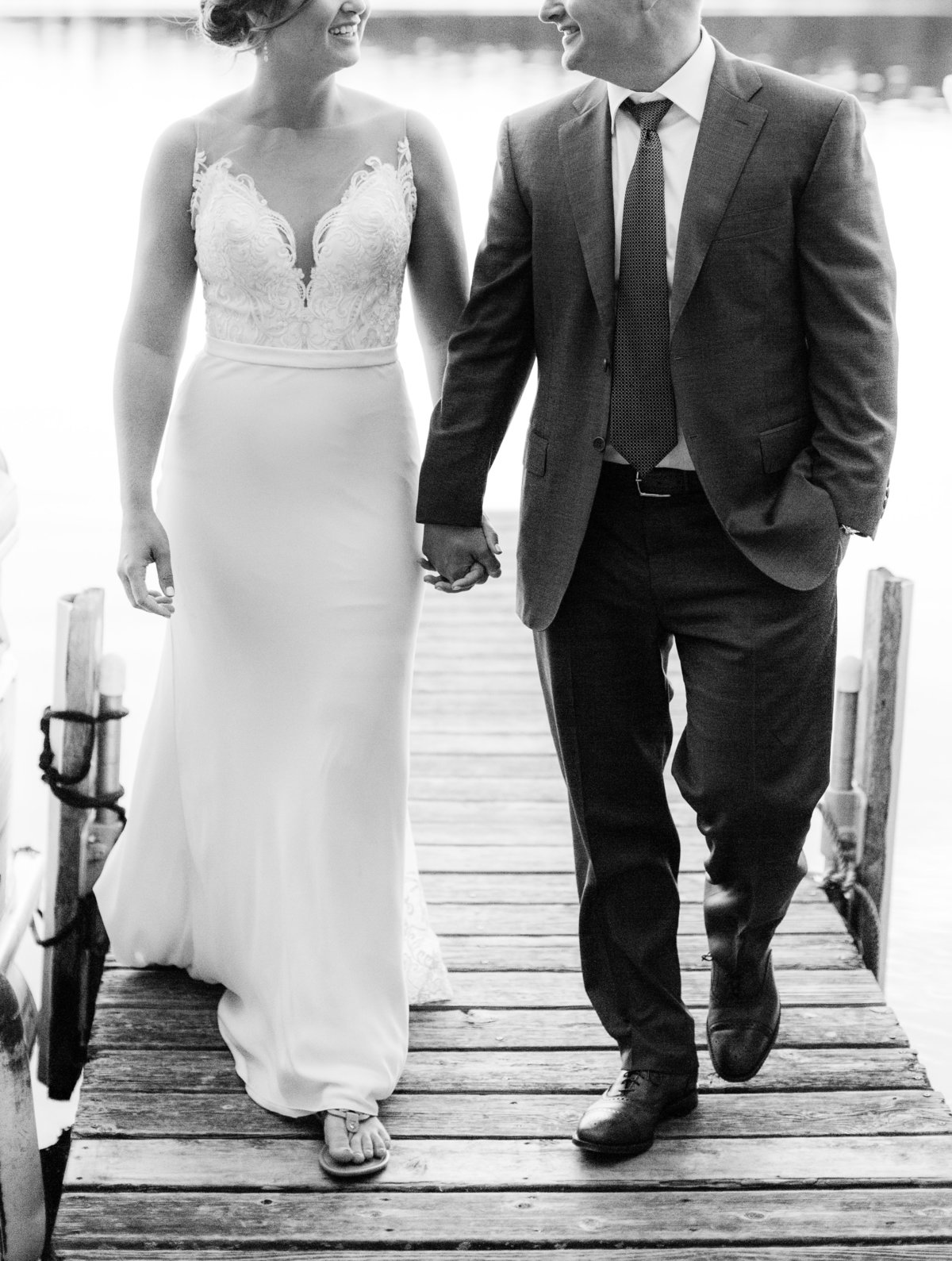 bride and groom walk hand in hand down dock to sherwood forest minnesota