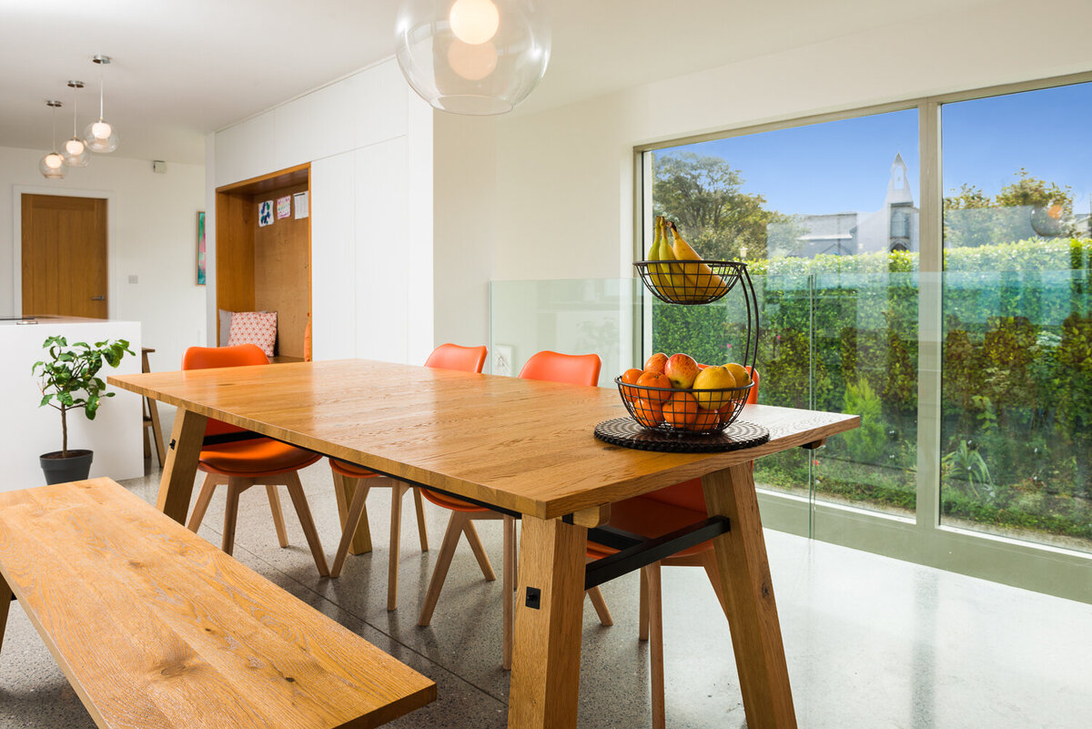 Wooden kitchen table and bench with orange chairs and floor to ceiling window