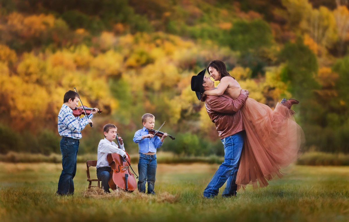 An engaged couple dancing in the mountains with three little boys serenading them with their violin, cello, and viola.