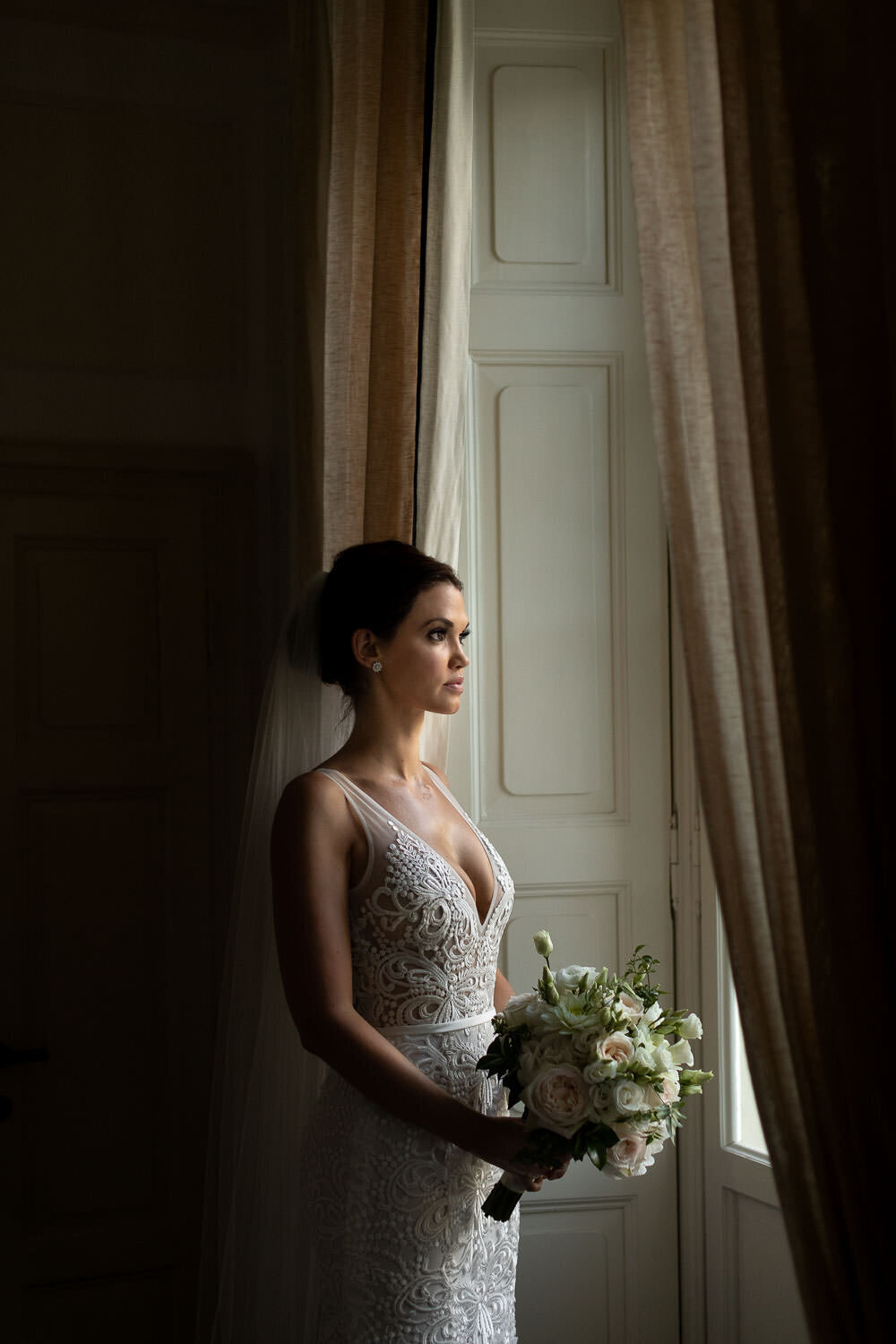 Bride holding floral bouquet in white lace wedding dress looking out window in lake Bride holding floral bouquet in white lace wedding dress looking out window in lake Como Wedding Italy Wedding Italy