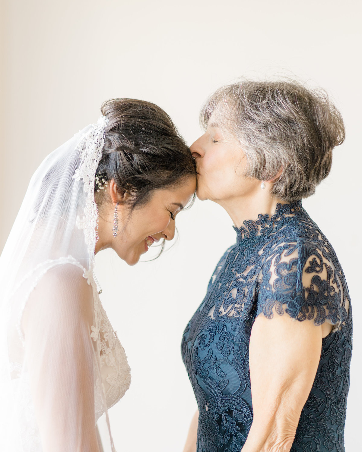 bride-being-kissed-by-mom-wedding-photo