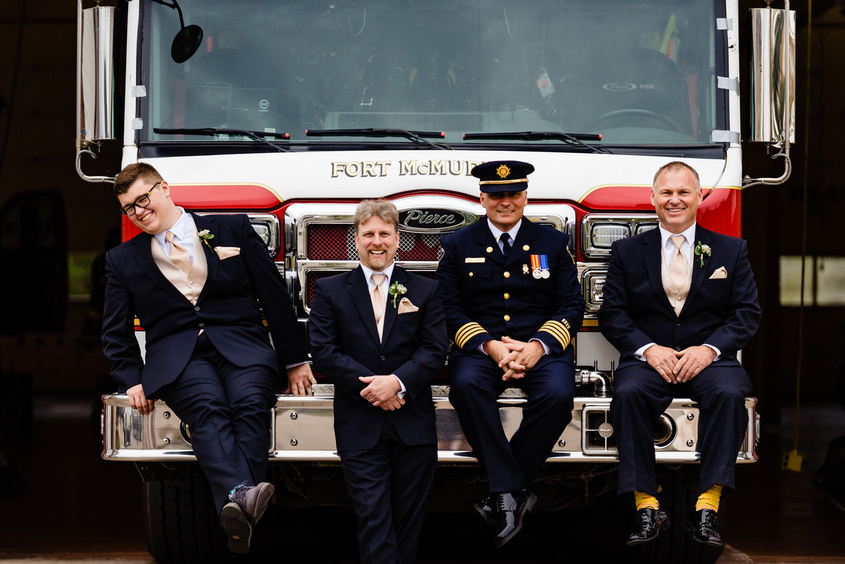 Groom and groomsmen sitting on a fire truck