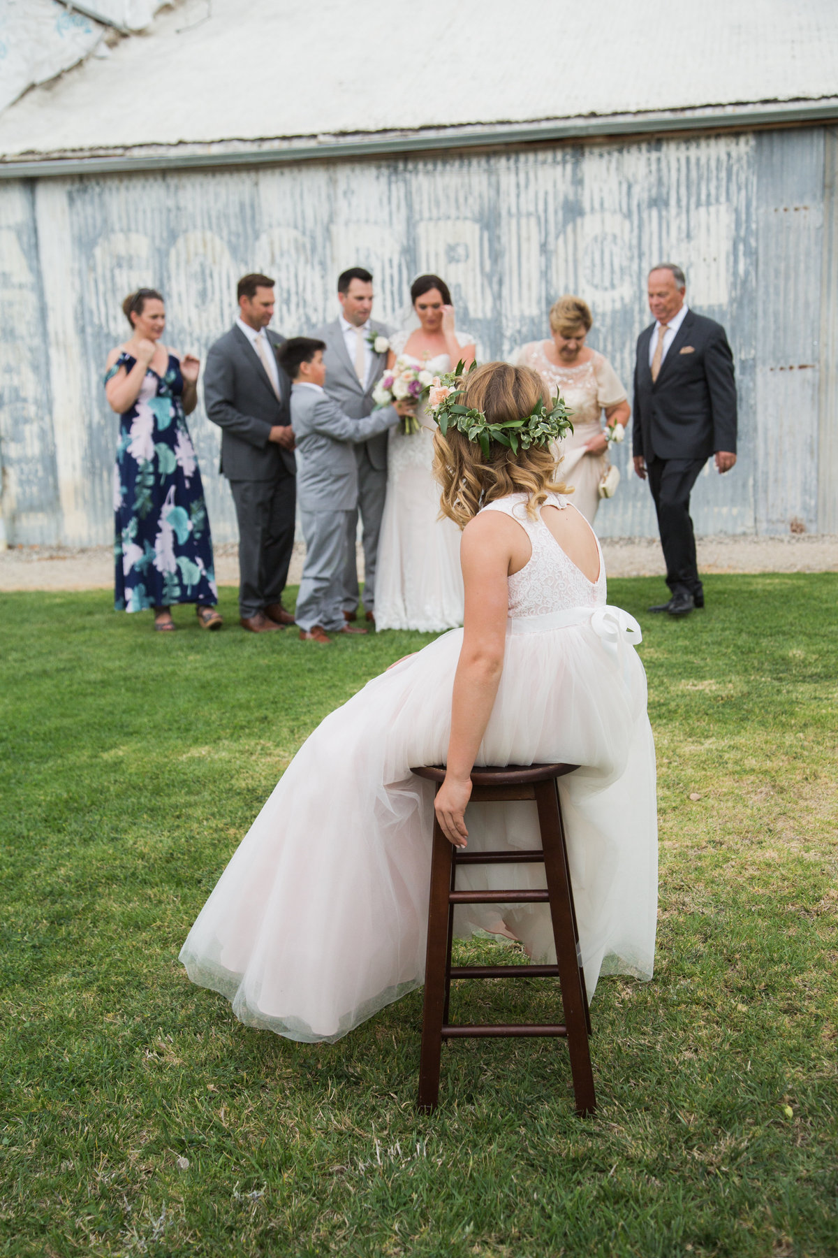 Flower girl sits infront of family formal photos at 1880 Union Hotel Wedding