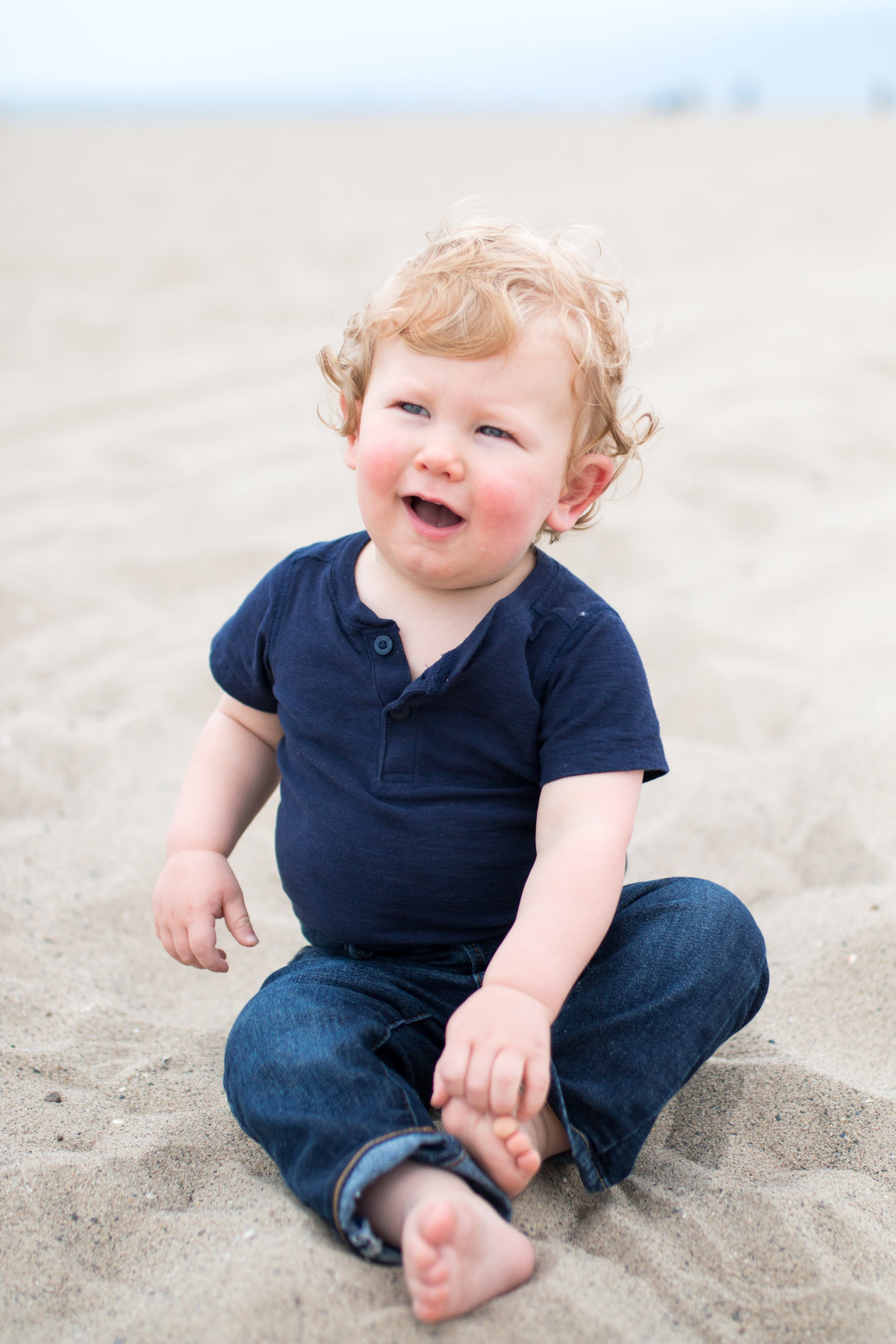 Beach family photography with toddler in sand