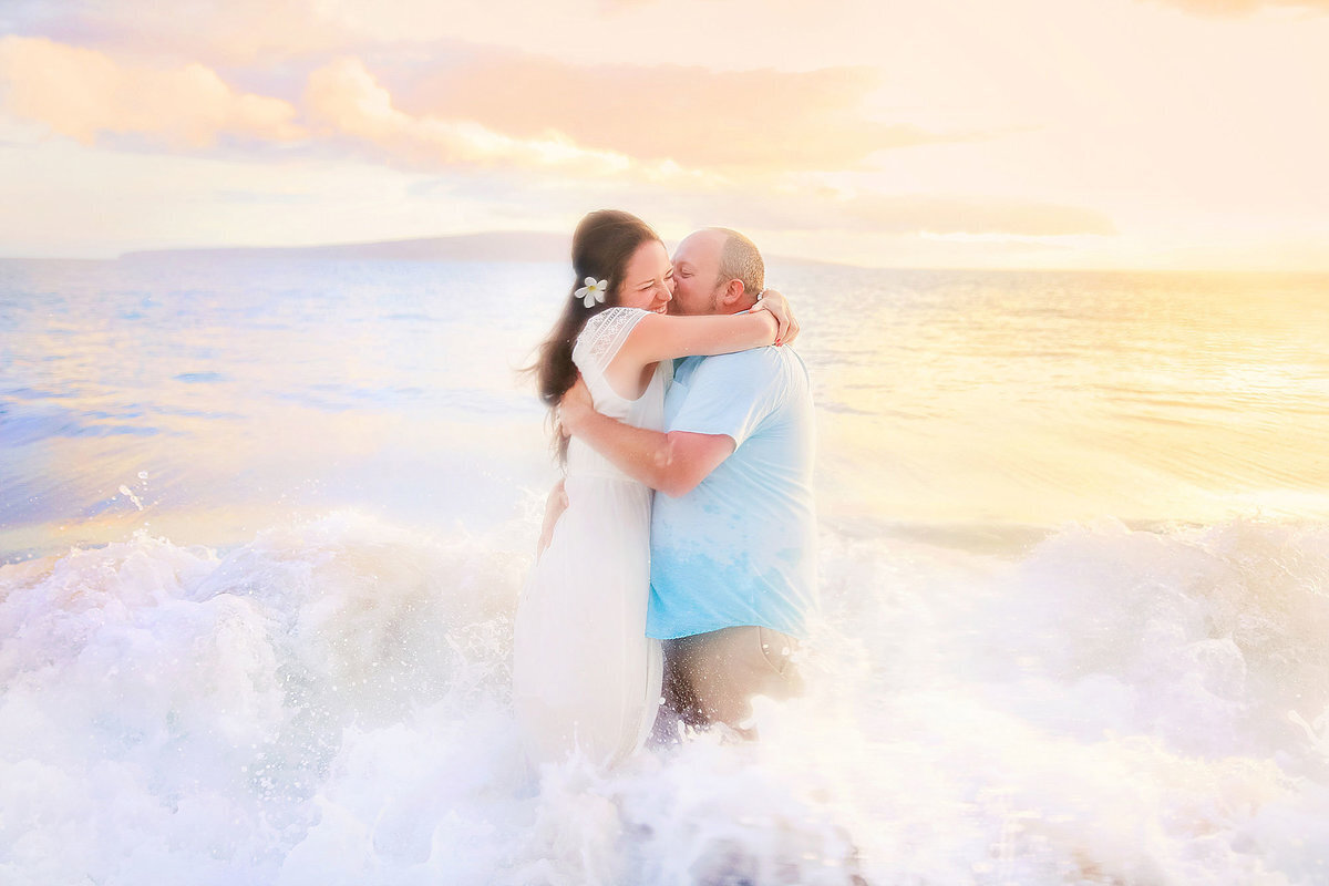 Maui engagement portrait of husband and wife being splashed by ocean and laughing