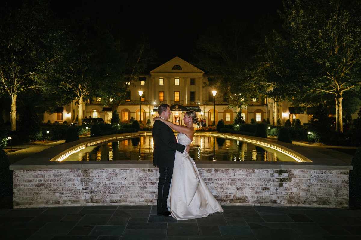 Happy Wedding Couple  Hugging in front of reflection pond