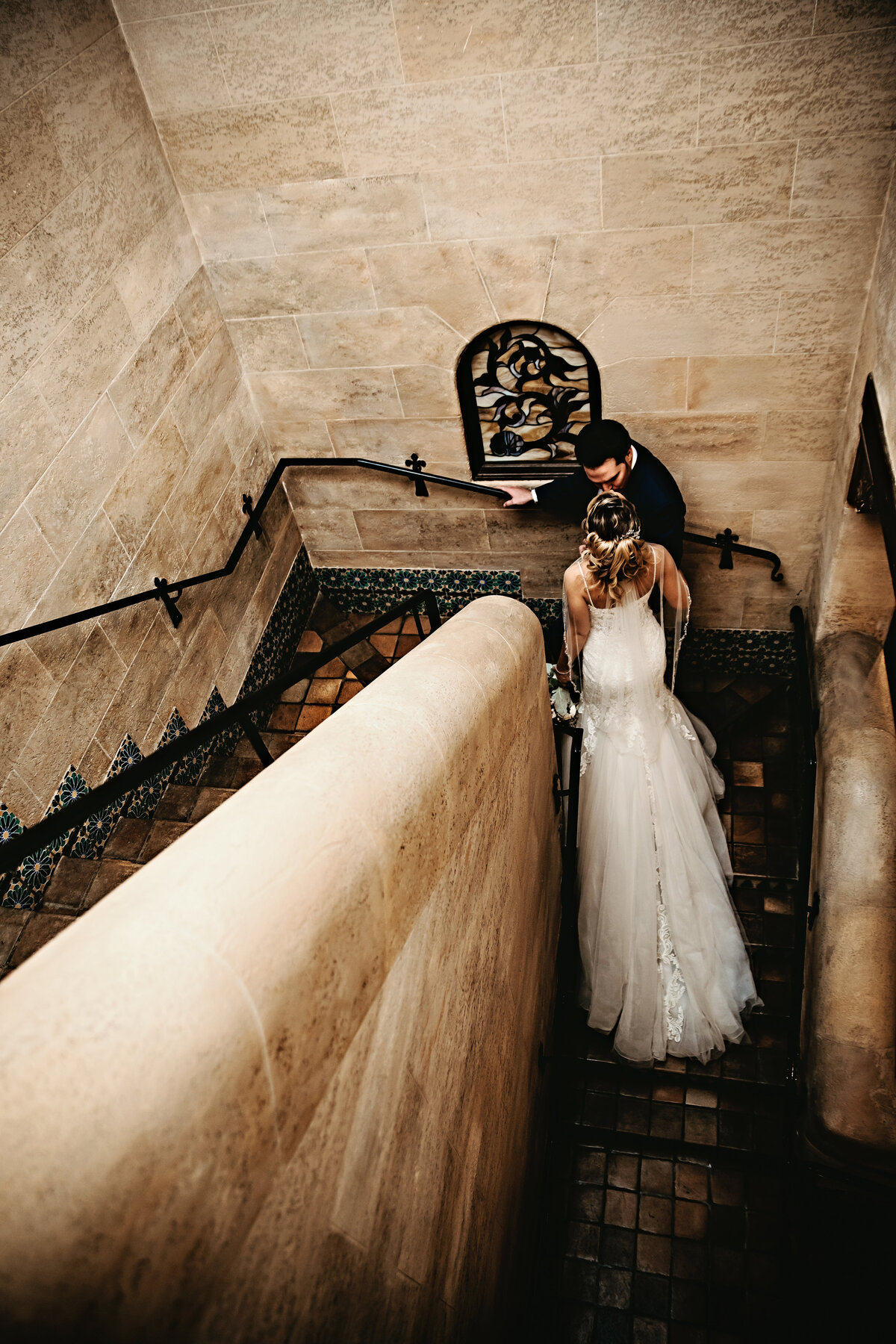 A picture of the bride and groom in a private moment, climbing a vintage stone stairway at their wedding venue, showing the wedding dress from behind by Garry & Stacy Photography Co - Tampa wedding photographer