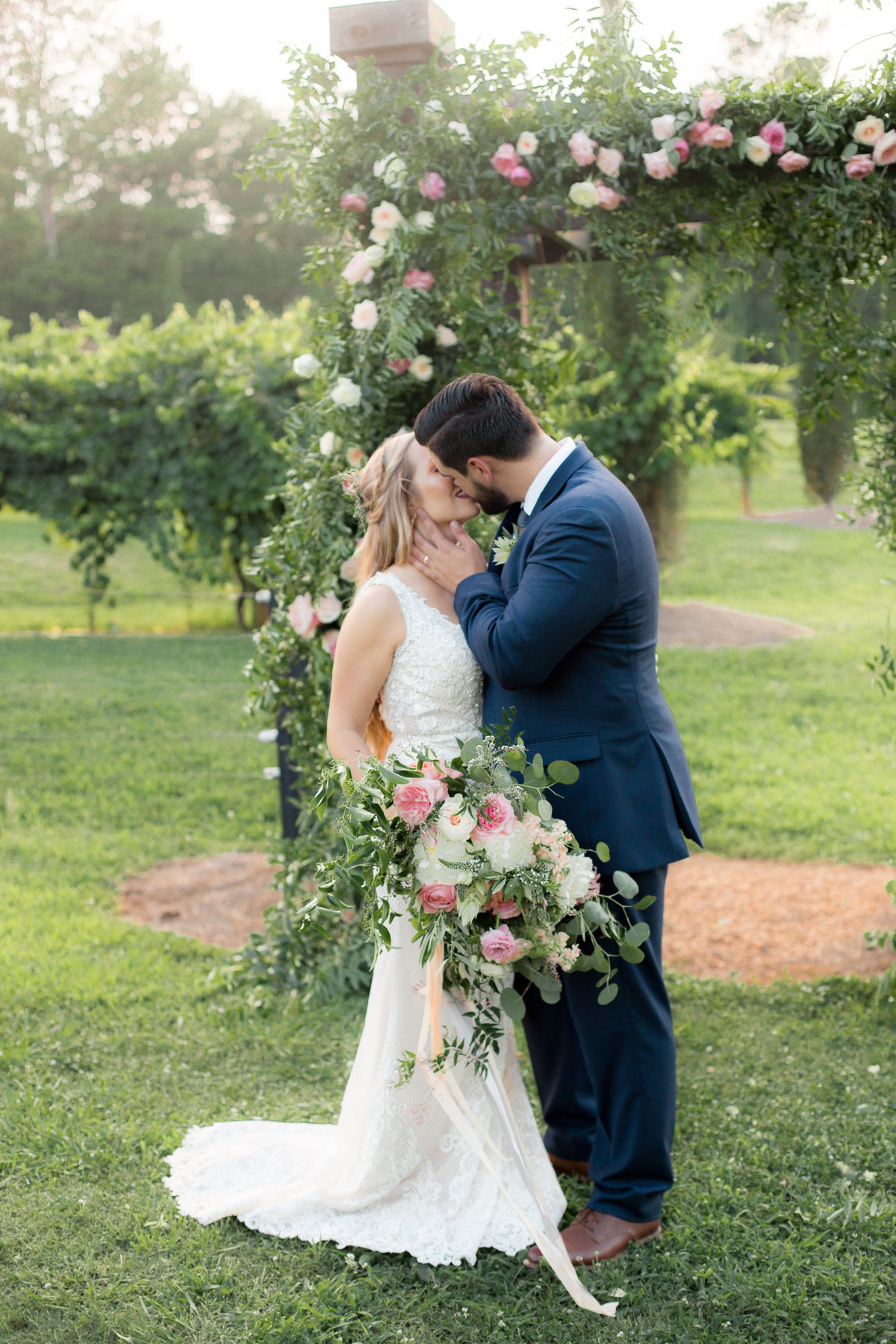 Bride and groom with bouquet in natural light vineyard