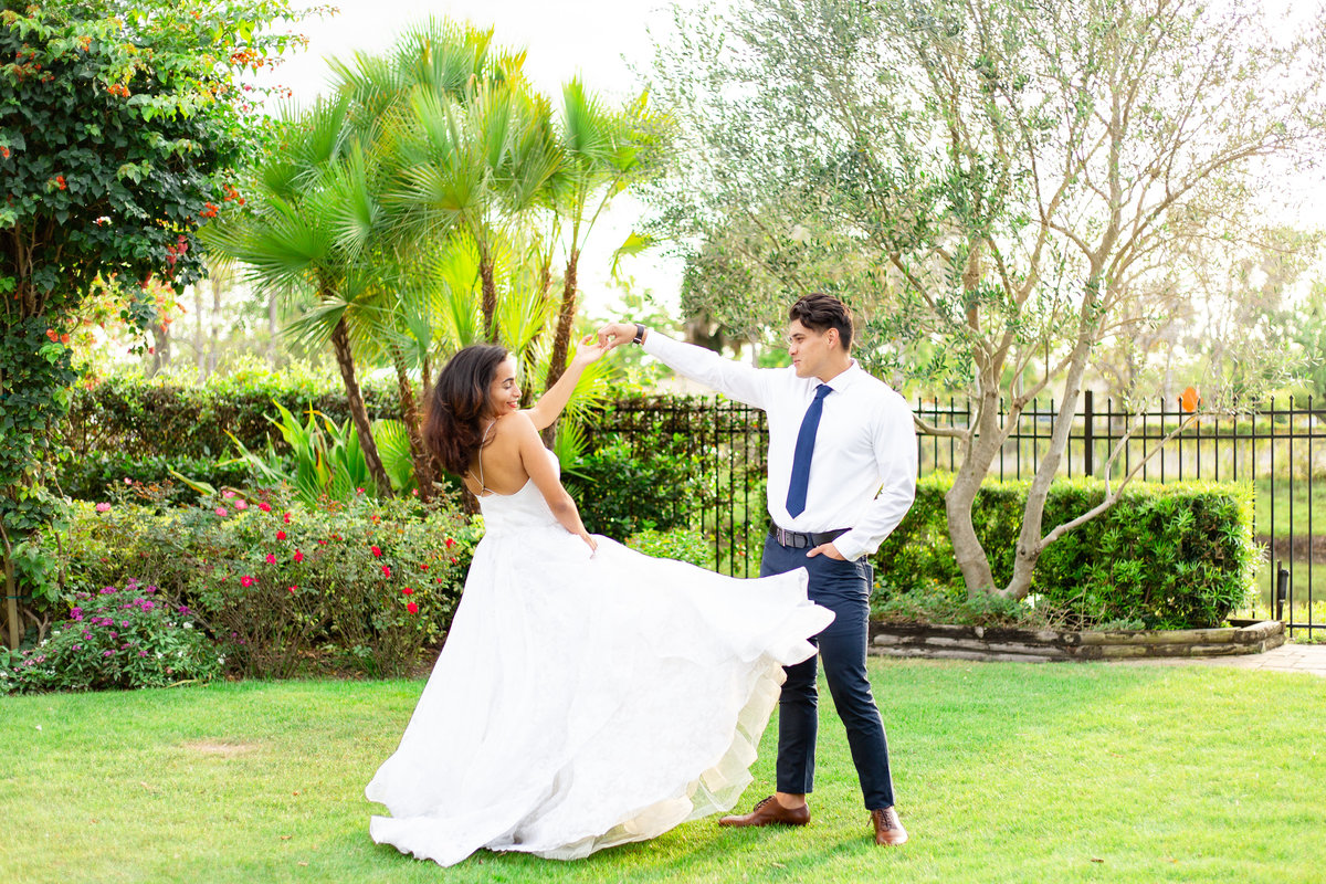 Groom twirls bride in flowing wedding dress at sunset at lush green field in at a romantic wedding venue