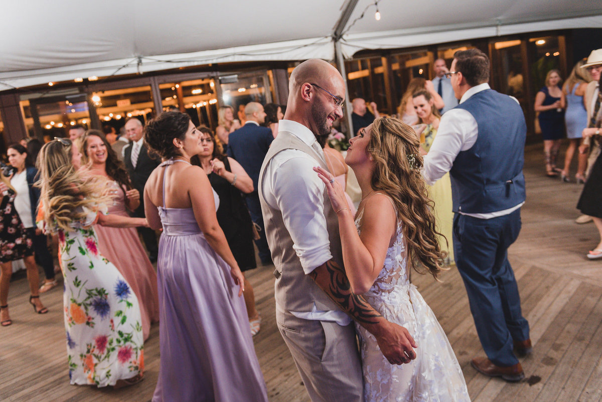 photo of bride and groom dancing with all the guests during wedding reception at Pavilion at Sunken Meadow