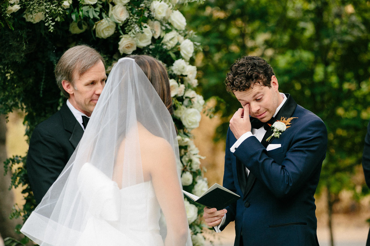 emotional groom reading vows to bride during wedding ceremony altar