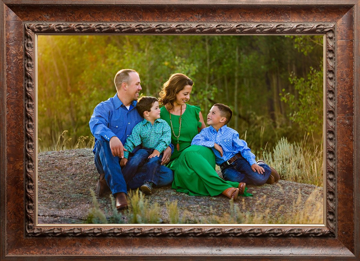 Family with two boys sitting on a rock at Vedauwoo mountains that are cuddling together on a warm and golden summer evening.