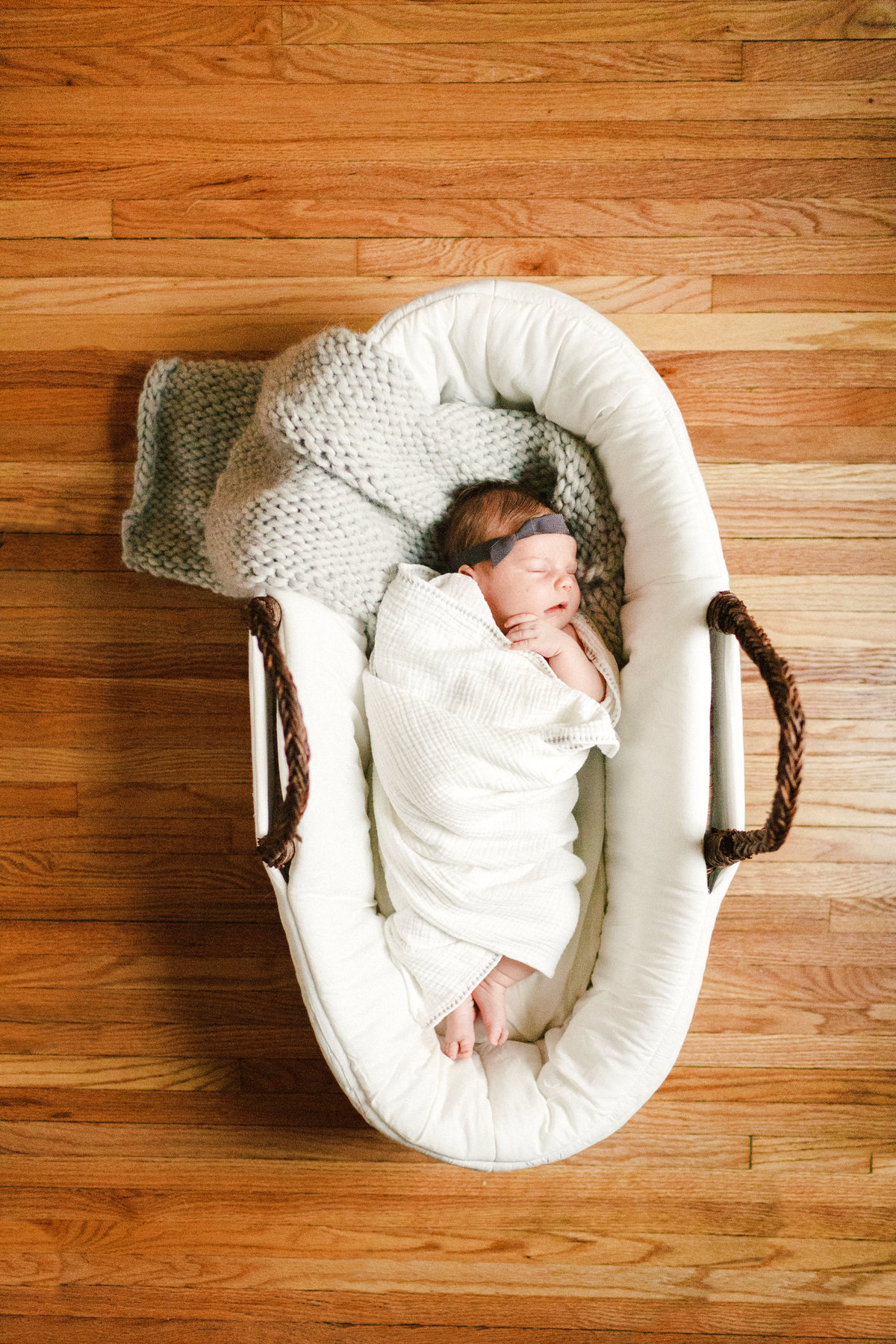 sleeping baby girl in a basket on wood floors for lifestyle newborn photography twin cities minnesota