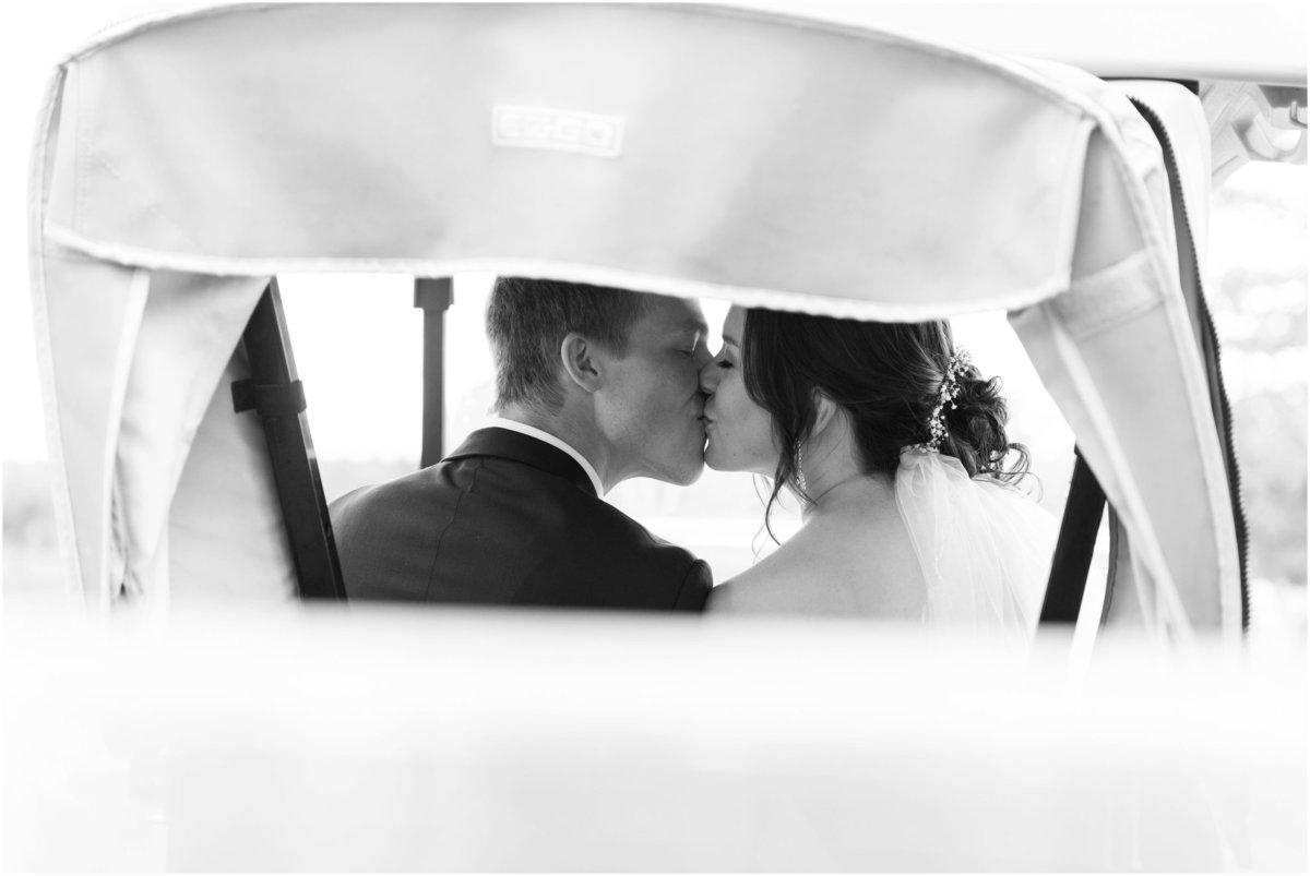 Bride and groom kissing in golf cart, black and white photography
