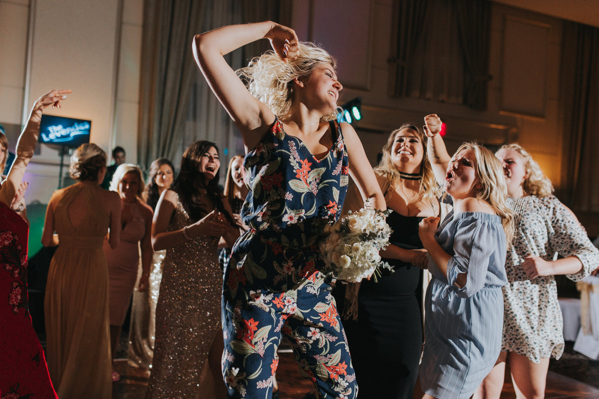 A guest catches the brides bouquet and jumps for joy