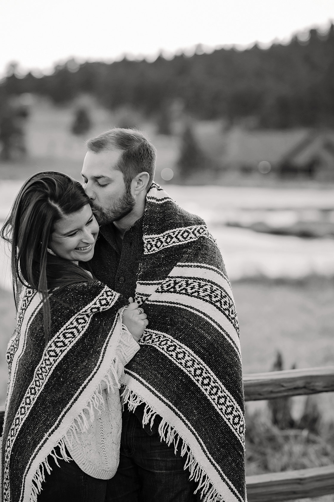 engaged couple covered in blanket