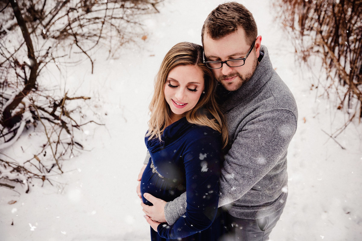 Expecting couple hugging in the snow
