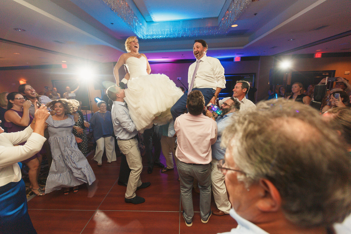 Bride and Groom Lifted into the Air in Chairs at their Traditional Jewish Wedding in Atlantic Beach Florida