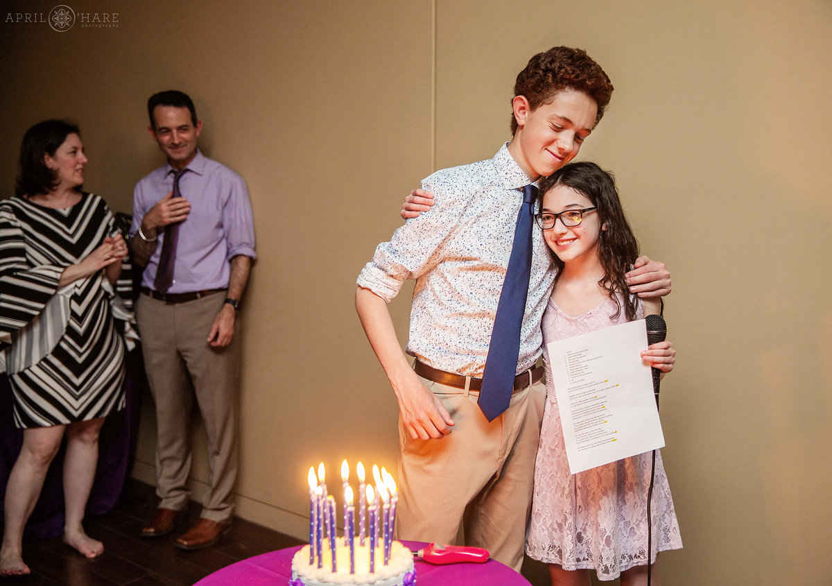 Brother hugs sis during bat mitzvah candle lighting at History Colorado in Denver