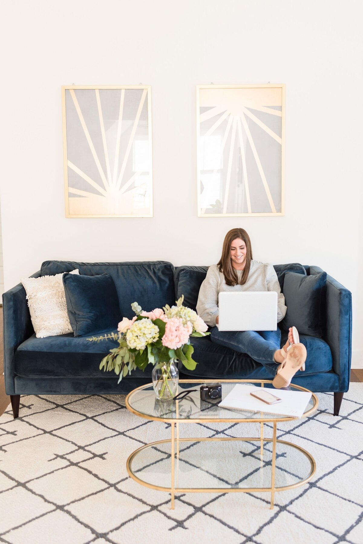 Woman working on her laptop in a Nashville Airbnb sitting on a blue velvet couch