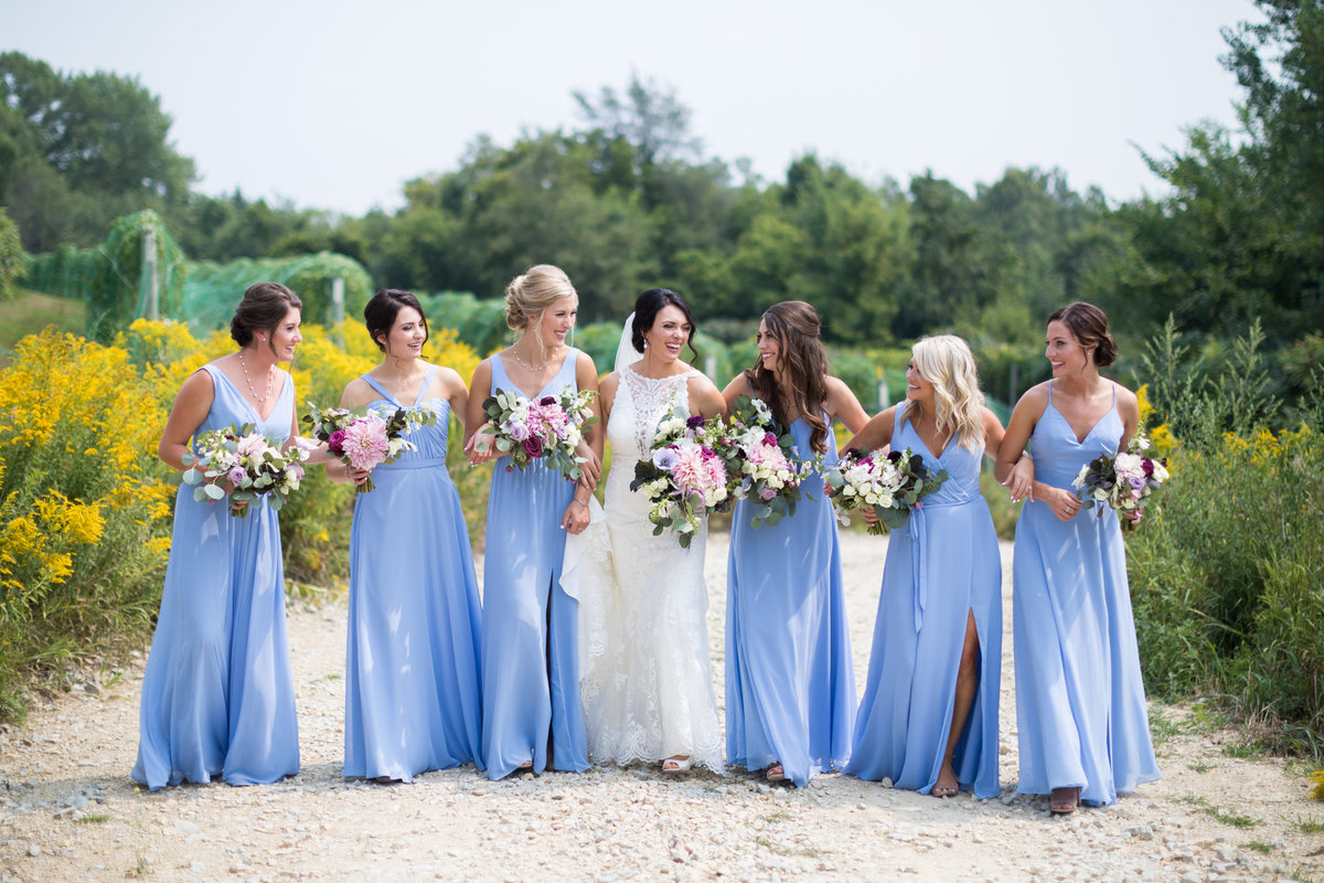 Bridesmaids with the softest shade of blue on a gravel road in the midwest