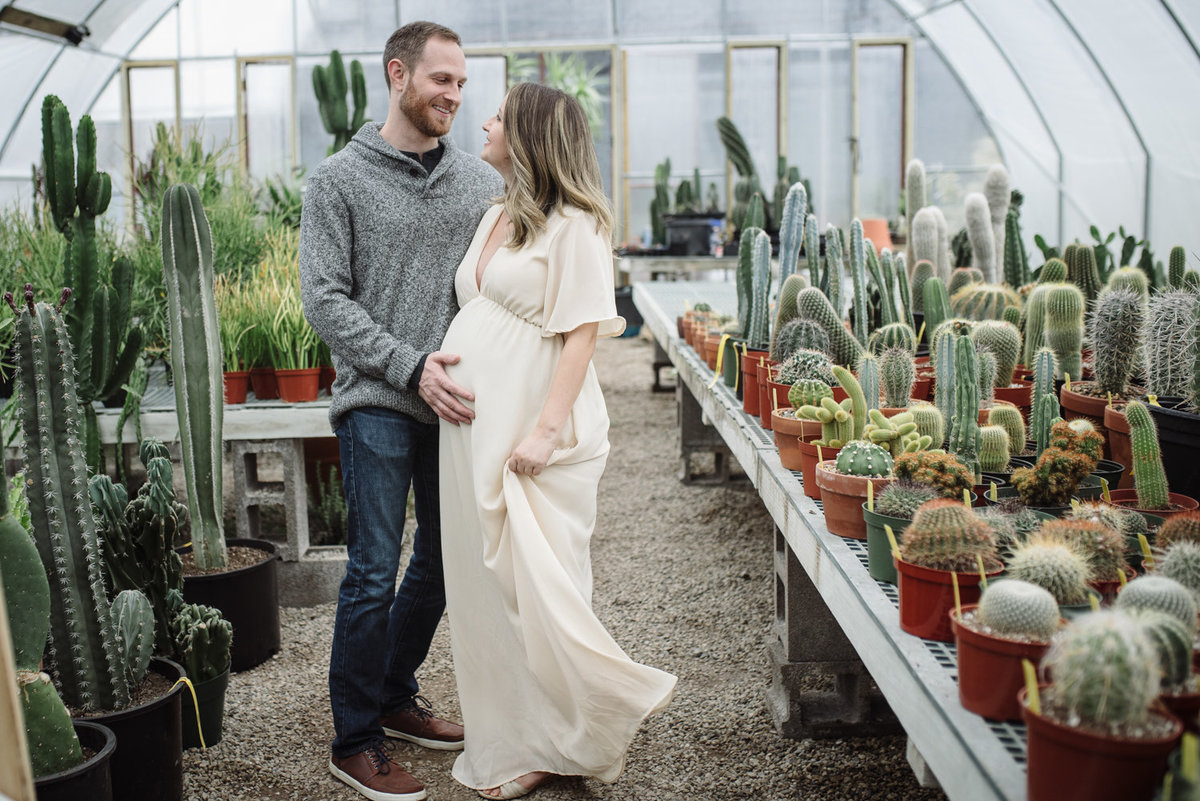 Expectant Parents are taking their maternity portraits in a Garden Center filled with succulents and expectant mother is wearing a cream colored maternity dress