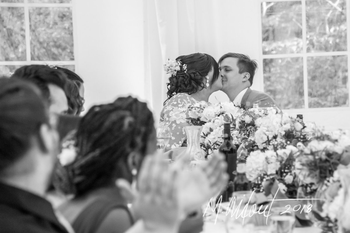 bride and groom kiss at the head table