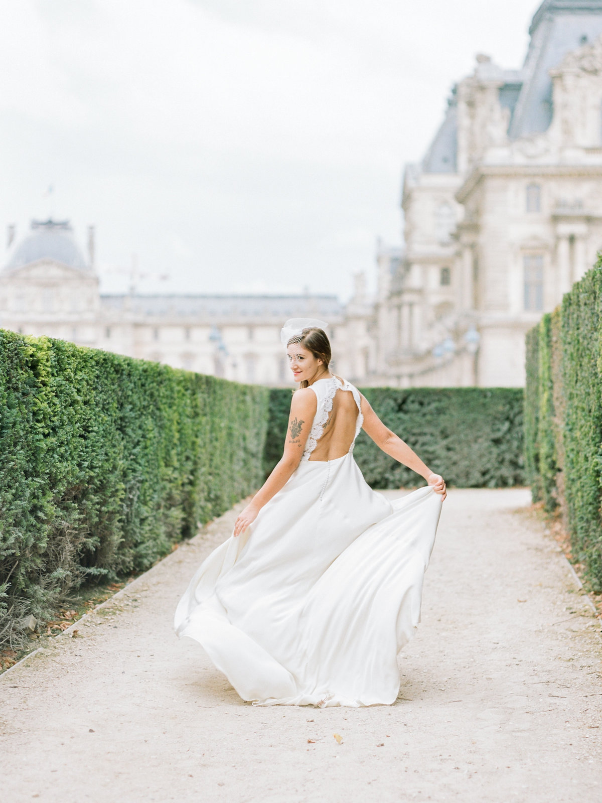 bride walking in front of the louvre with an open back dress