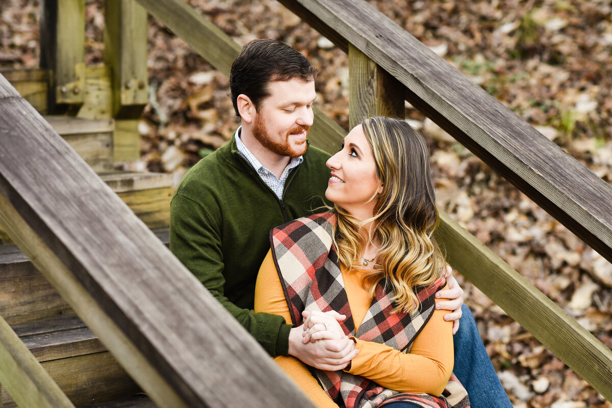 Beautiful Mississippi Engagement Photography: couple sits on wooden staircase in fall clothing