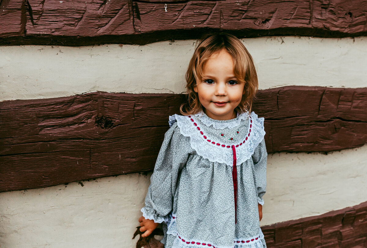 Child in front of log cabin