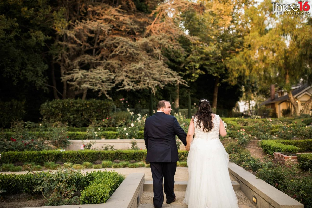 Bride and Groom take a walk holding hands on the grounds of the Richard Nixon Library wedding venue
