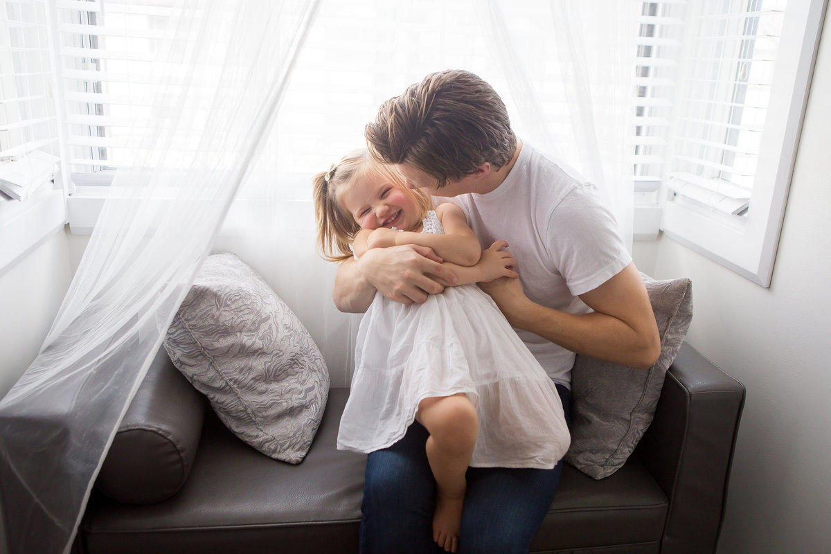 Father snuggling and tickling toddler daughter {Oakville Lifestyle Photographer}