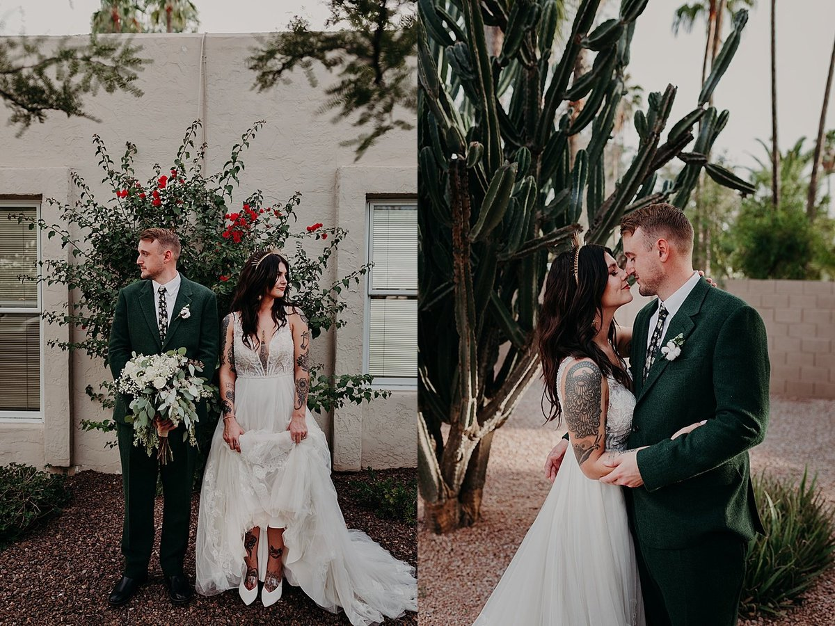 Tattooed bride in a wedding dress and tattooed groom in a green suit stand side by side and look in opposite directions
