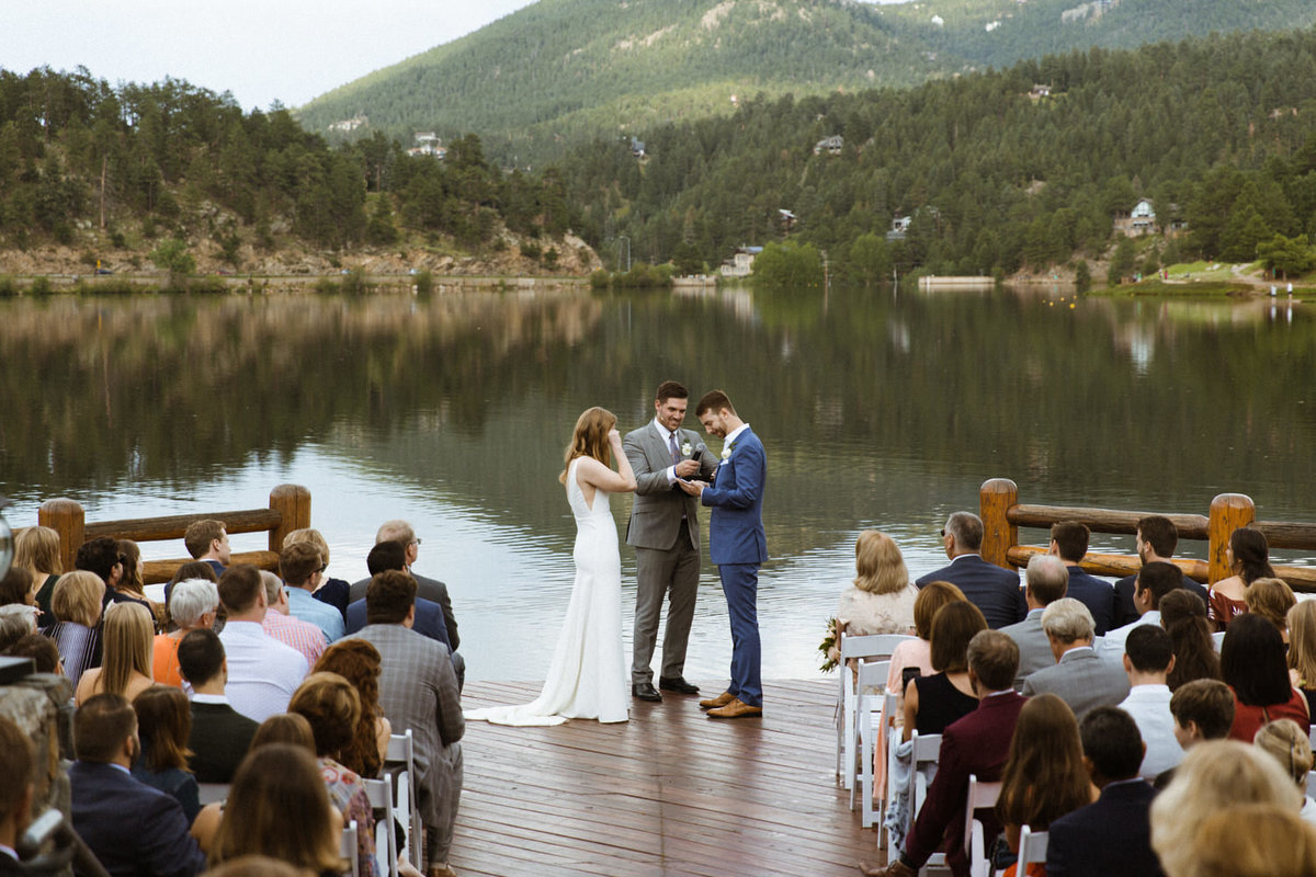 A bride wipes her eye while getting married on a lakeside pier to a mountain backdrop
