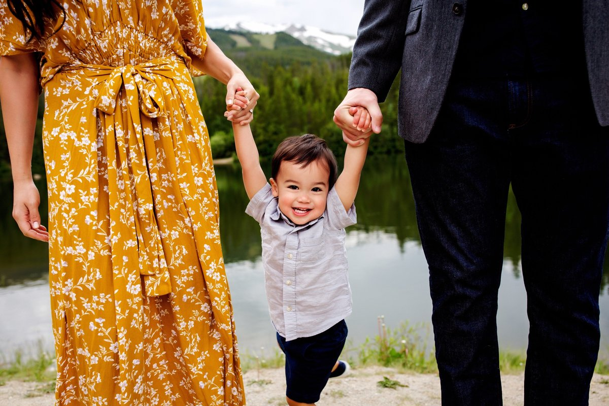 Little boy holding parents hands in Colorado