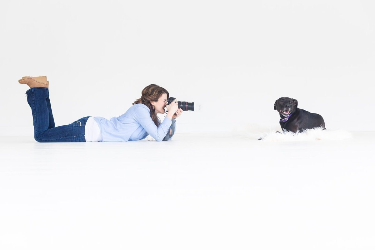 woman photographs dog while lying down in white indoor studio