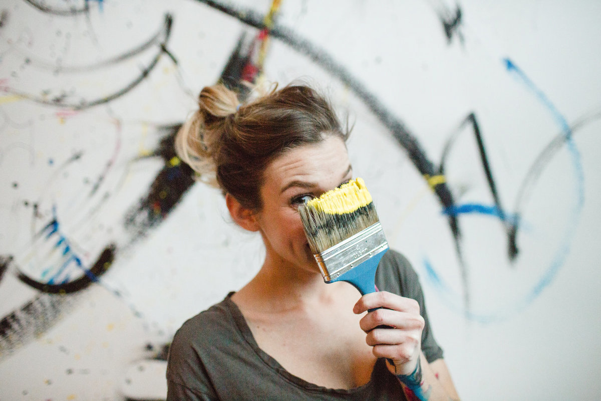 artist portrait of artist holding brush of paint up to face